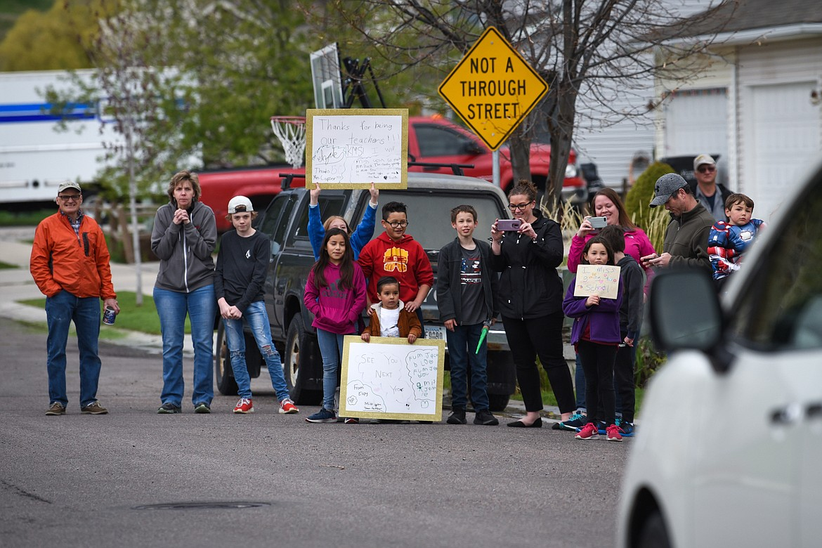 Families hold signs and watch a parade of Rankin Elementary School teachers and staff through the neighborhood along Bluestone Drive in Kalispell on Thursday, May 7. (Casey Kreider/Daily Inter Lake)