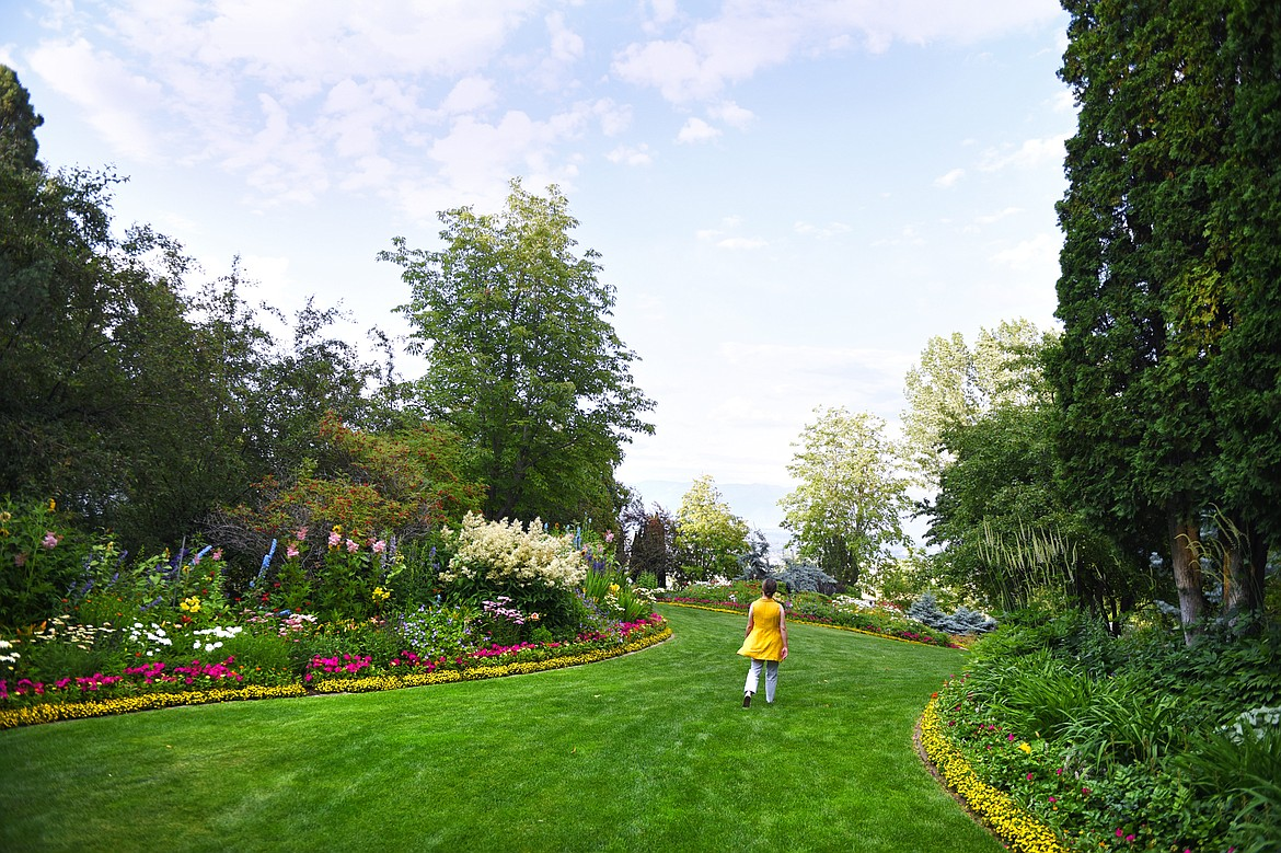A visitor walks along a garden path full of blooming flowers during a Splendid Summer Evenings self-guided visit at Bibler Home and Gardens in Kalispell on Wednesday, July 22. Possible dates for future self-guided visits include their Sweet Summer Days on Aug. 3-4, though all tickets must be purchased in advance. (Casey Kreider/Daily Inter Lake)
