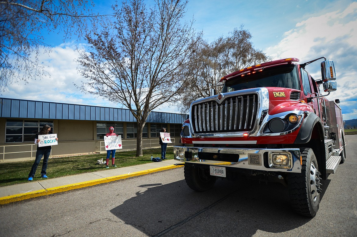 South Kalispell firefighters drive through a parade for K-5 students and teachers outside Stillwater Christian School in Kalispell on Friday, April 24. (Casey Kreider/Daily Inter Lake)