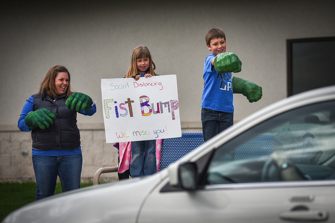 Stillwater Christian School bookkeeper Amy Orem and her daughter and son, Maddie and Henry, hold a sign and give fist bumps with Incredible Hulk hands during a parade for K-5 students and teachers outside the school on Friday, April 24. (Casey Kreider/Daily Inter Lake)