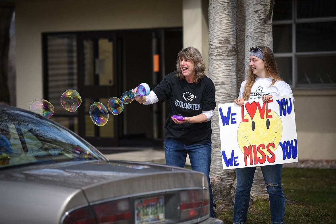 Stillwater Christian School Title I teacher Leslie Hodgskiss and her daughter Linnea, a senior at the school, hold signs and blow bubbles for passing students and parents during a parade for grades K-5 outside the school on Friday, April 24. (Casey Kreider/Daily Inter Lake)