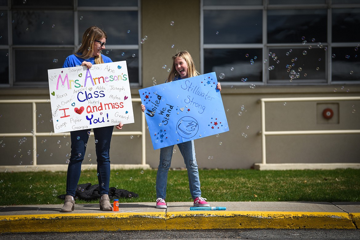 Stillwater Christian School kindergarten teacher Erin Arneson and her daughter Ariahna wave signs during a parade for K-5 teachers and students outside the school on Friday, April 24. (Casey Kreider/Daily Inter Lake)