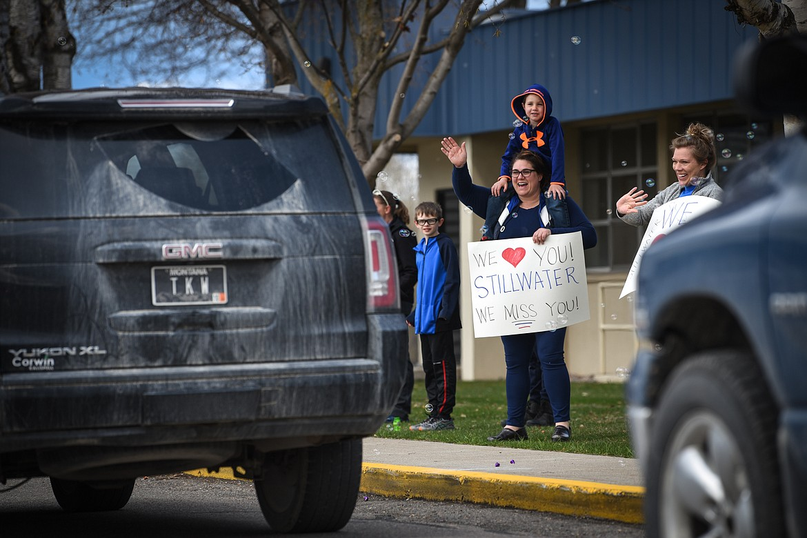 Stillwater Christian School fourth-grade teacher Rya Diede and her son Cal wave to students and parents during a parade for grades K-5 outside the school on Friday, April 24. (Casey Kreider/Daily Inter Lake)