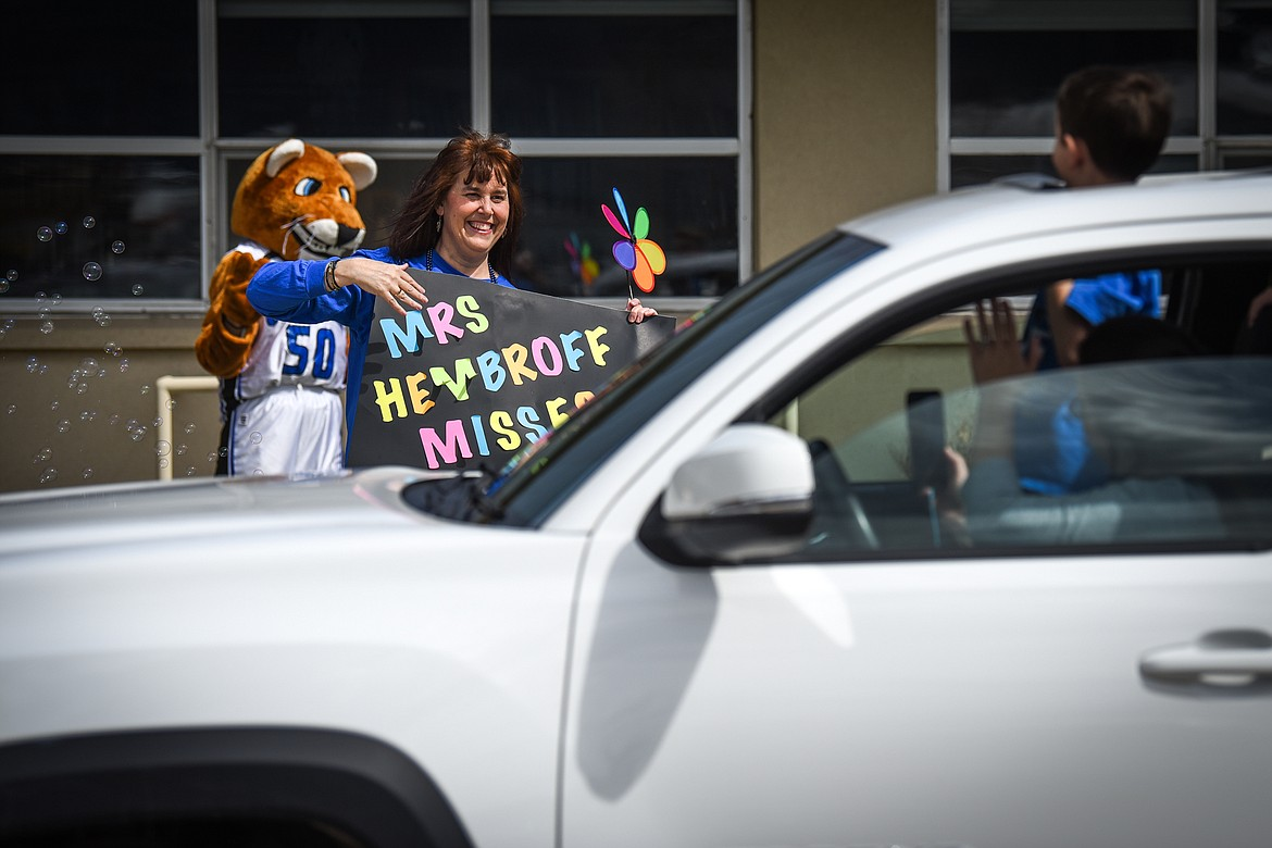 Stillwater Christian School kindergarten teacher Jill Hembroff waves and smiles to passing students and parents during a parade for grades K-5 outside the school on Friday, April 24. (Casey Kreider/Daily Inter Lake)
