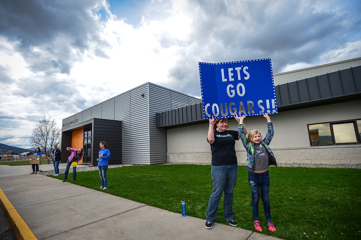 Summer Van Oort, Director of Learning Services at Stillwater Christian School, and her daugther, Madeline, a fourth-grader at the school, hold a sign during a parade for K-5 teachers and students outside the school on Friday, April 24. (Casey Kreider/Daily Inter Lake)