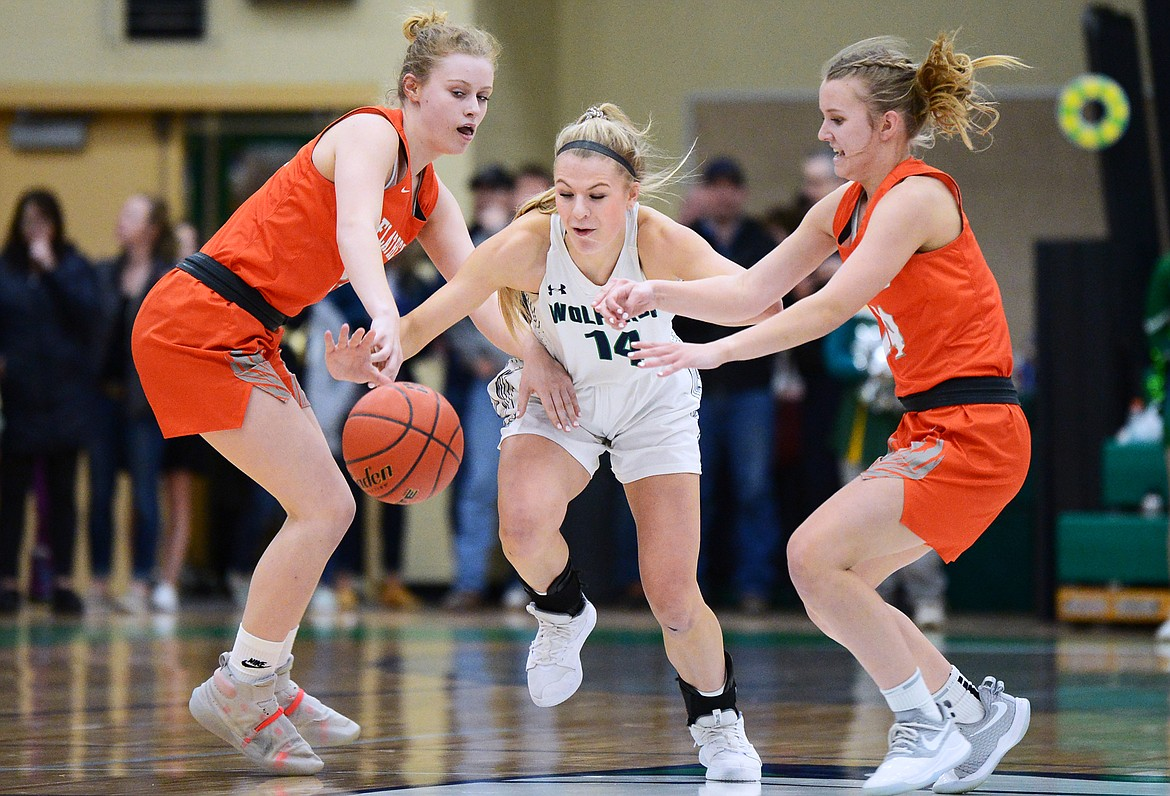 Glacier's Aubrie Rademacher (14) fights for a loose ball with Flathead's Molly Winters (34) and Jenna Johnson (14) during a crosstown matchup at Glacier High School on Friday. (Casey Kreider/Daily Inter Lake)