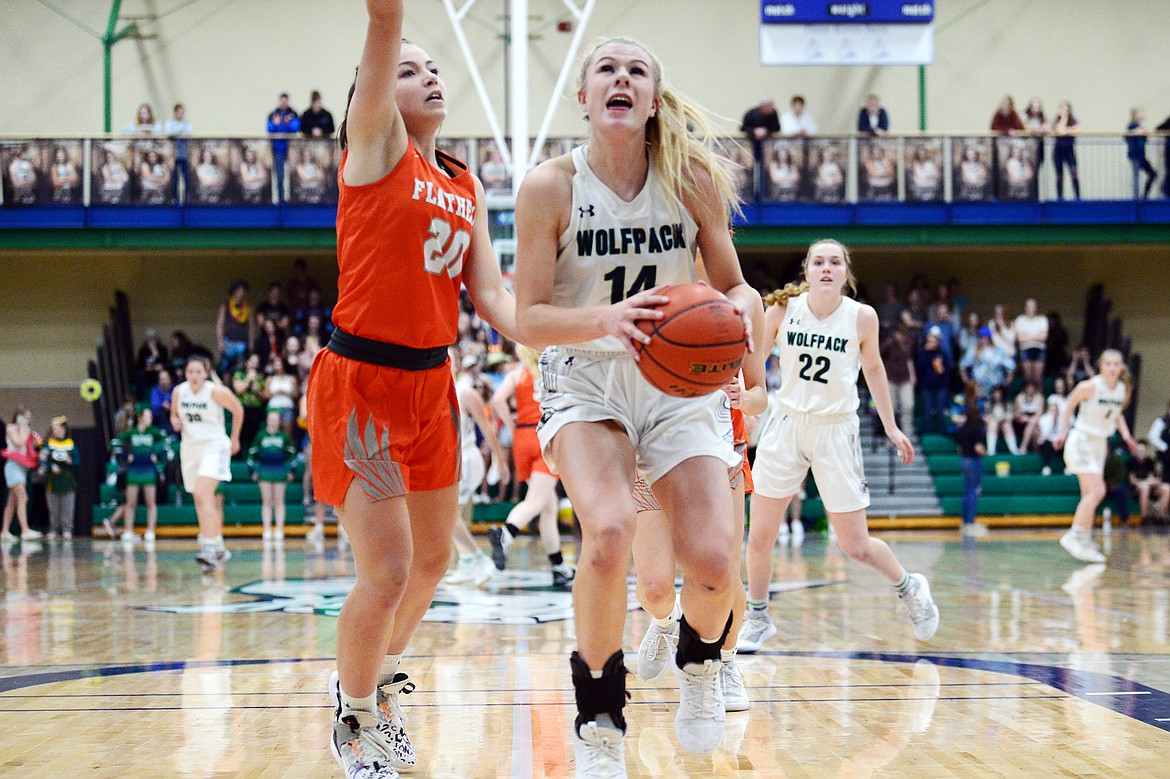 Glacier's Aubrie Rademacher (14) drives to the basket against Flathead's Bridget Crowley (20) during a crosstown matchup at Glacier High School on Friday. (Casey Kreider/Daily Inter Lake)