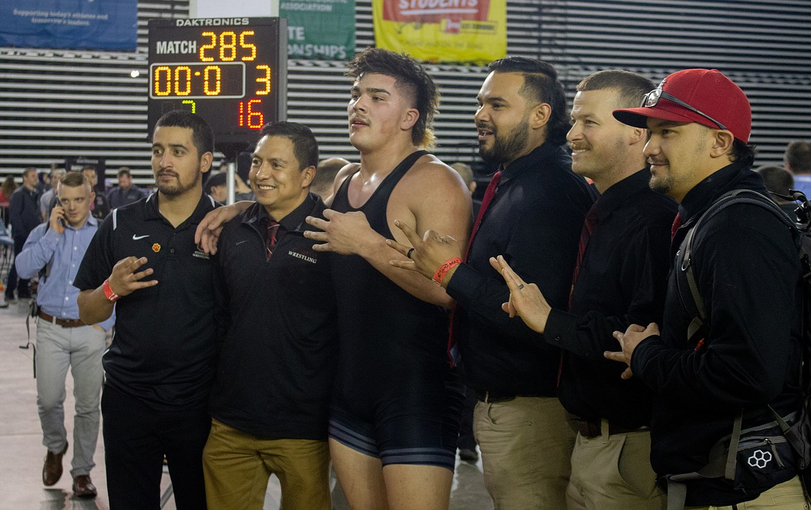 """Casey McCarthy/Columbia Basin Herald Isaiah Perez and his Othello coaching staff hold up the """"threes"""" to celebrate the senior becoming the first three-time state champion in school history with his w"""