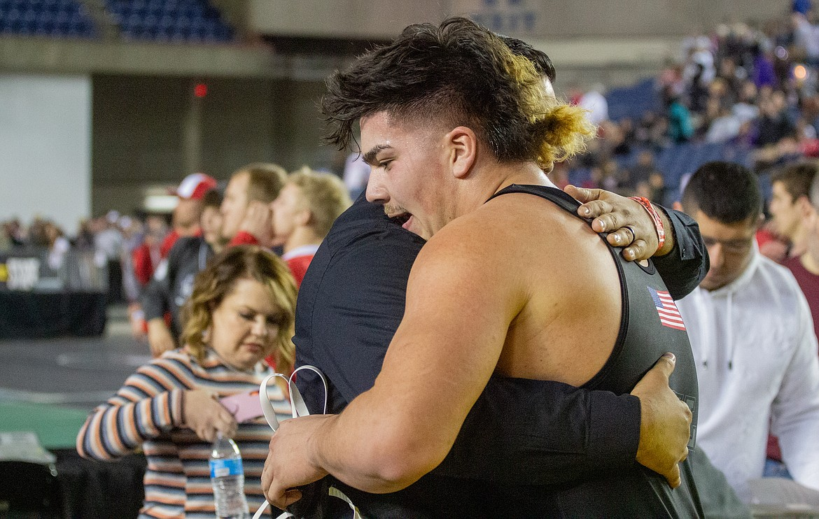 Casey McCarthy/Columbia Basin Herald Othello's Isaiah Perez embraces head coach Rudy Ochoa II after claiming his third title in his final bout on the mat on Saturday in Tacoma.