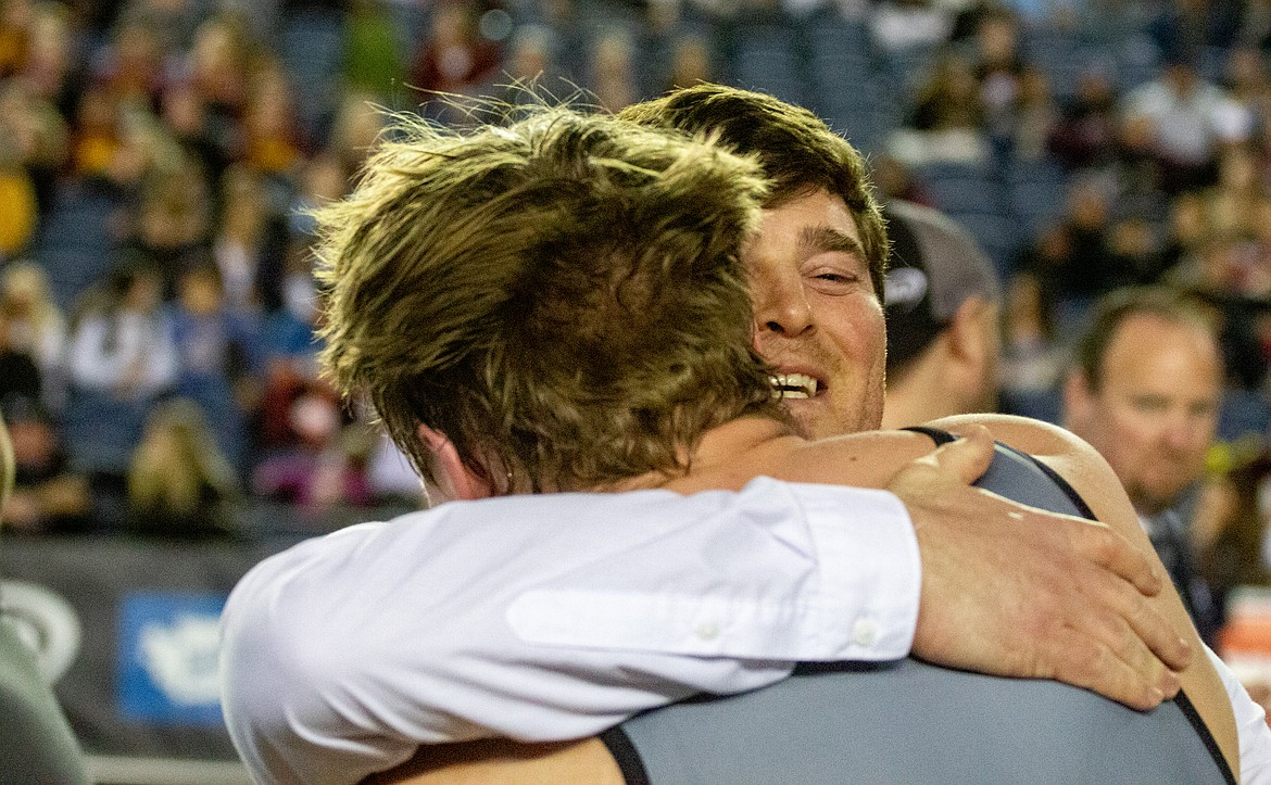 Casey McCarthy/Columbia Basin Herald Ephrata head coach Patrick Mitchell smiles as he hugs his senior and state champion, Mac Laird, after his match on Saturday in Tacoma.