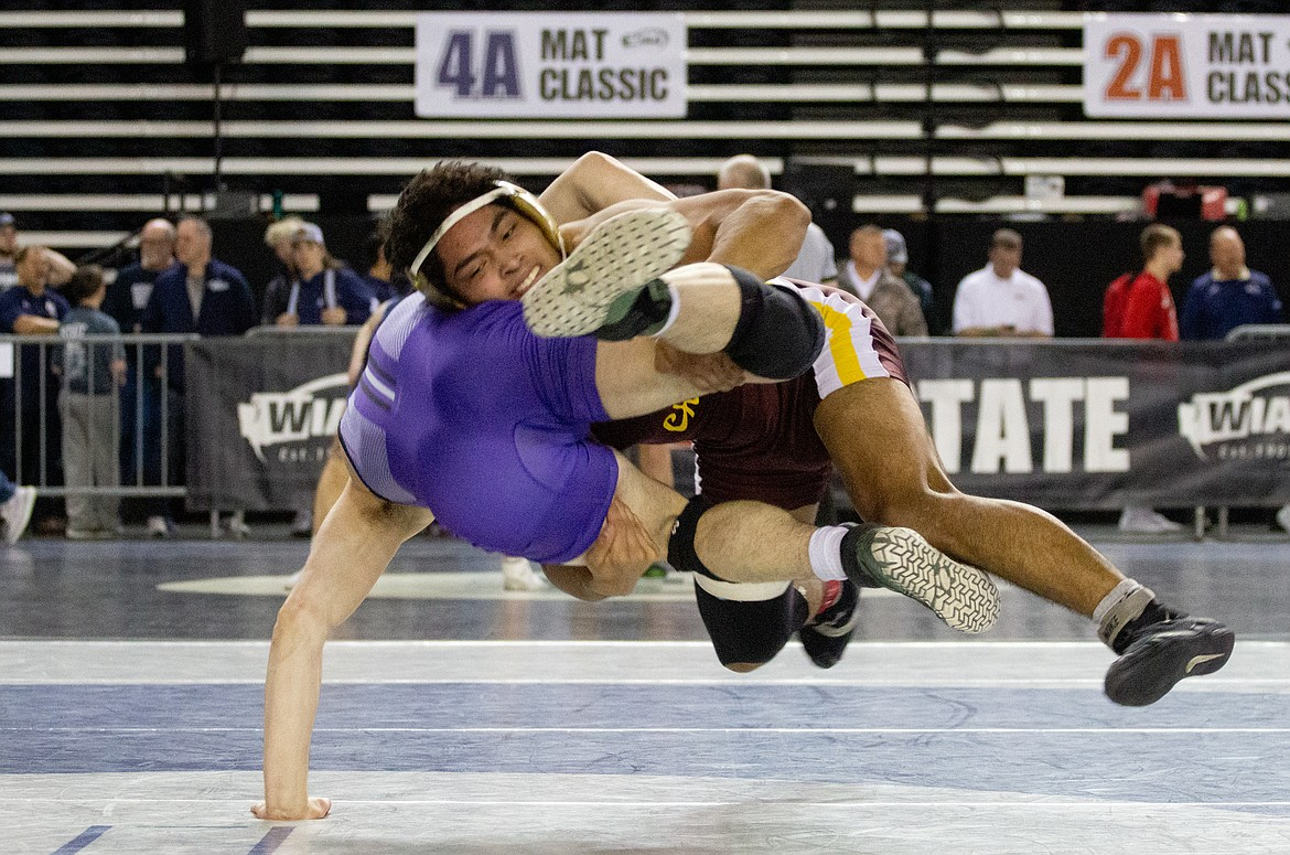 Casey McCarthy/Columbia Basin Herald Moses Lake's Cruz Vasquez hangs midair before taking his opponent to the mat in the third-place bout on Saturday at the  Mat Classic XXXII.