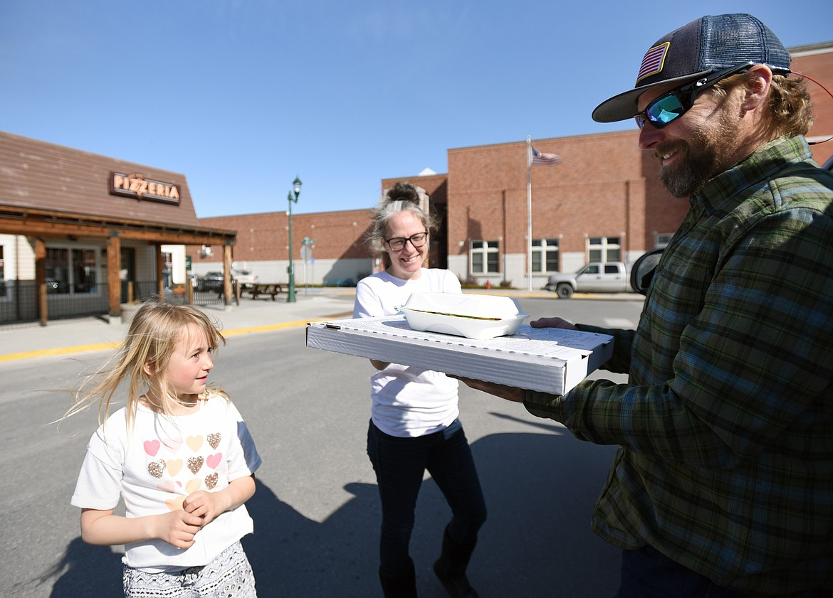 Chris Brooks, right, and his daughter Bella pick up a takeout order from Becky Ojennes at Jersey Boys Pizzeria in Whitefish on March 19. On Thursday, the Flathead City-County Health Board voted to close all bars, restaurants, casinos and fitness facilities to the public for at least 10 days in an effort to fight the coronavirus pandemic, but many restaurants have converted to curbside pickup service. (Casey Kreider/Daily Inter Lake)