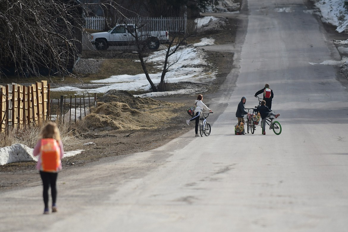 Students walk home with the day's lunch, tomorrow's breakfast and a week's worth of spring break groceries in Martin City on Thursday, March 19. (Teresa Byrd/Hungry Horse News)