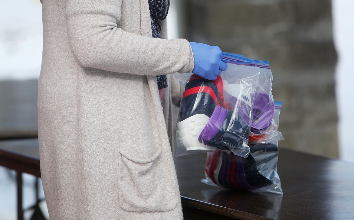 An employee picks up a bag of N95 masks donated by Trevor Seals on Friday morning at the Summit Medical Fitness Center. (Mackenzie Reiss/Daily Inter Lake)