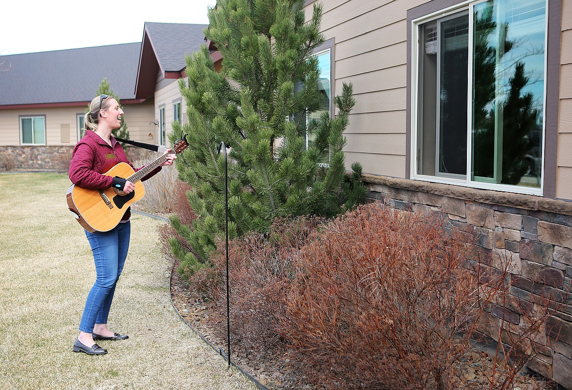 $ID/NormalParagraphStyle:Kirsten Wells plays guitar for residents of Rising Mountains Assisted Living in Bigfork.