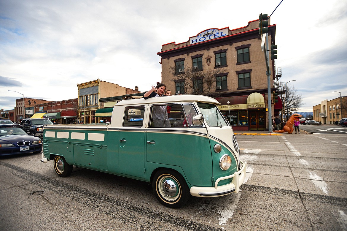 Passengers wave from a classic Volkswagen during the Kruise Kalispell event on Main Street on Friday, April 17. (Casey Kreider/Daily Inter Lake)