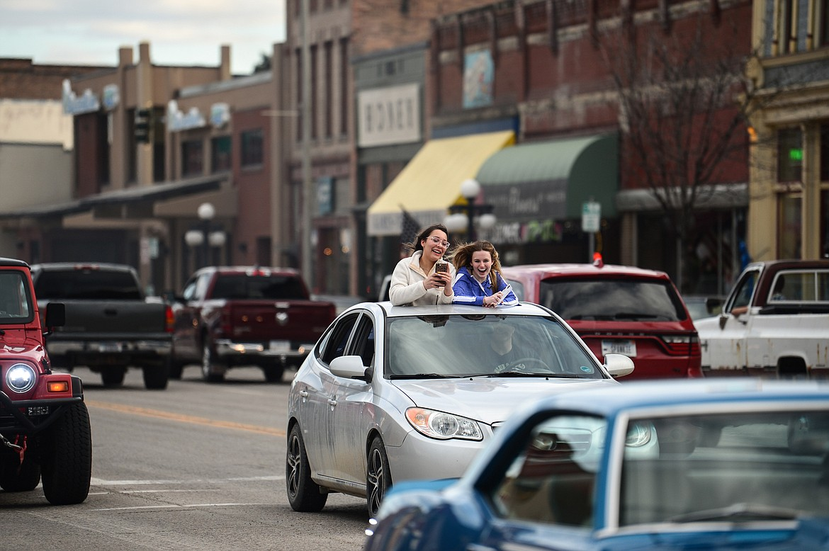 Two girls stick out of the moonroof of a vehicle during the Kruise Kalispell event on Main Street on Friday, April 17. (Casey Kreider/Daily Inter Lake)