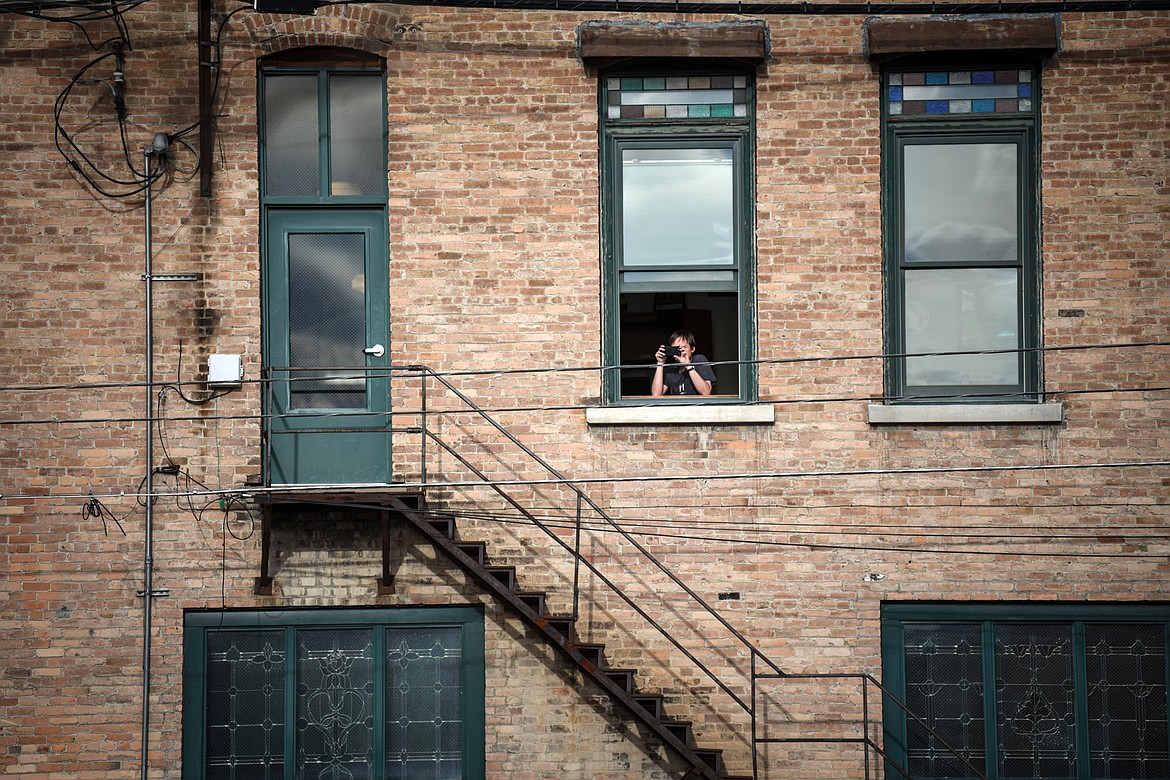 A spectator watches the Kruise Kalispell event from a second story window on Friday, April 17. (Casey Kreider/Daily Inter Lake)