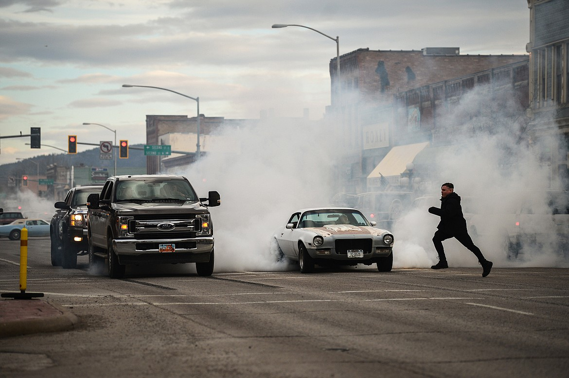Vehicles spin their tires at a traffic light on Main Street during the Kruise Kalispell event on Friday, April 17. (Casey Kreider/Daily Inter Lake)