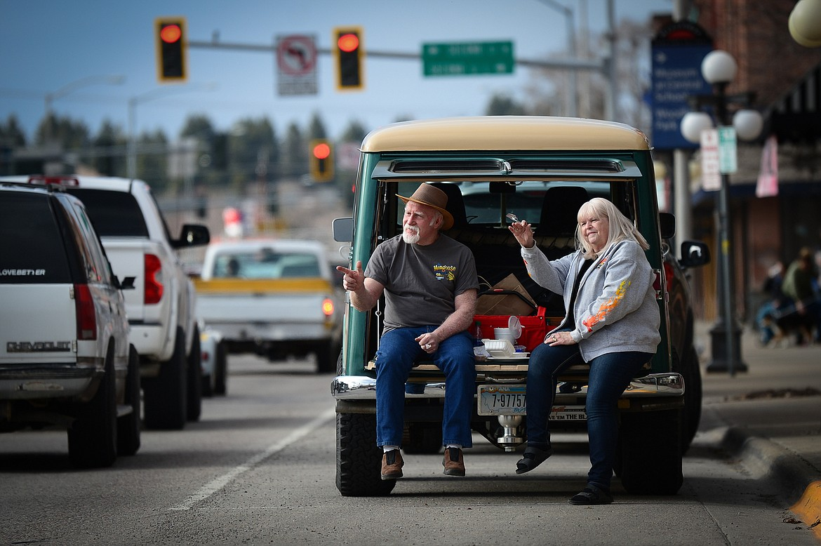 Mike and Jenise Lithgow, of Kila, wave to passing vehicles along Main Street during the Kruise Kalispell event on Friday, April 17. (Casey Kreider/Daily Inter Lake)