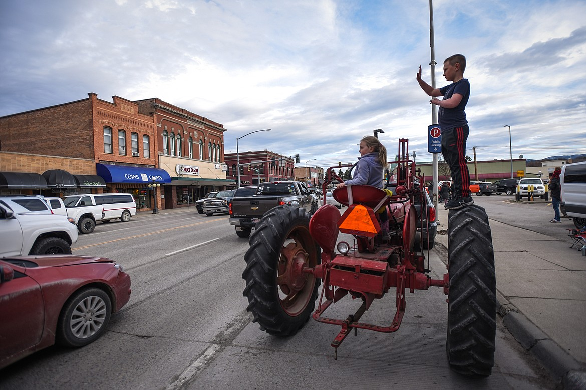 Children watch the Kruise Kalispell event along Main Street from a 1947 Farmall International tractor on Friday, April 17. (Casey Kreider/Daily Inter Lake)