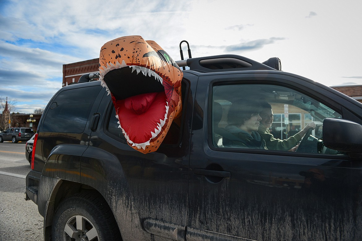 A vehicle with an inflatable Tyrannosaurus rex costume sticking out the window participates in the Kruise Kalispell event on Main Street on Friday, April 17. (Casey Kreider/Daily Inter Lake)
