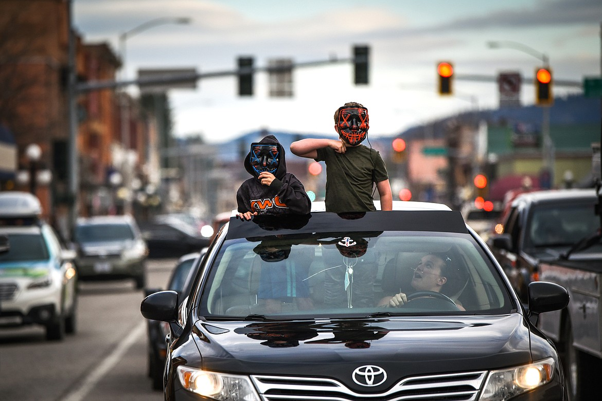 Two kids dance and wave out of a vehicle's moonroof during the Kruise Kalispell event on Main Street on Friday, April 17. (Casey Kreider/Daily Inter Lake)