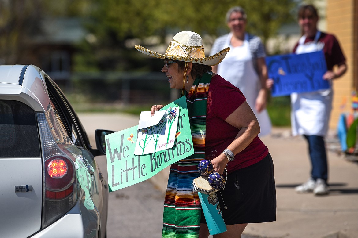 Kindergarten teacher Sue Stephens greets a student and parent during a Cinco de Mayo Parade for teachers, students and staff outside Swan River School in Bigfork on Tuesday. (Casey Kreider/Daily Inter Lake)