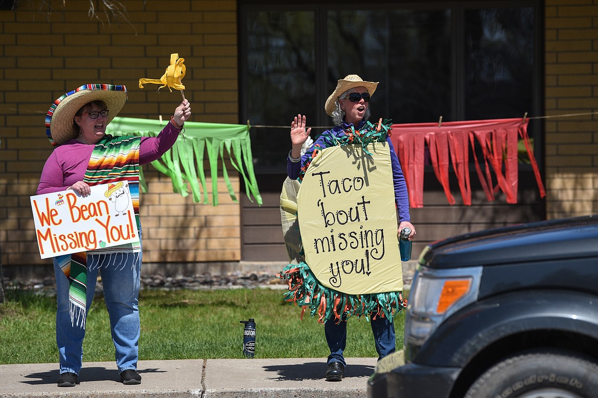 Second-grade teacher Sherry Bradstreet, left, and third-grade teacher Kate Butts wave and hold signs for students during a Cinco de Mayo Parade outside Swan River School in Bigfork on Tuesday. (Casey Kreider/Daily Inter Lake)