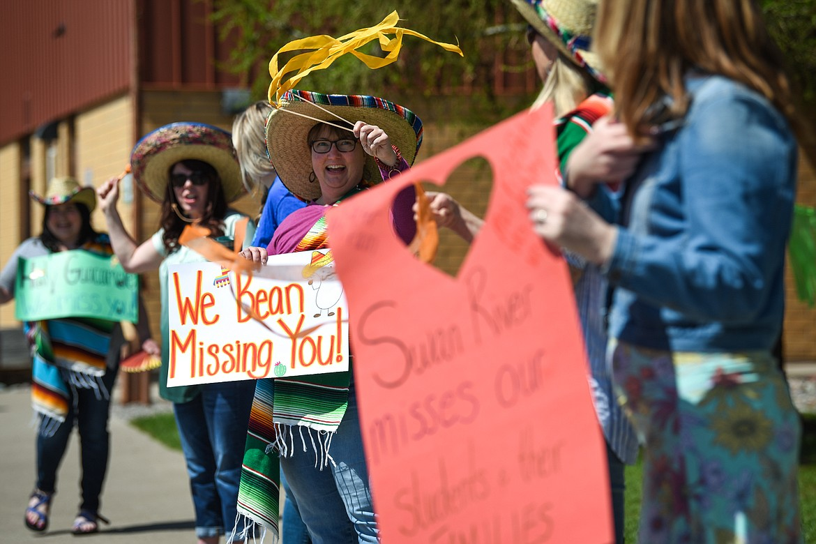 Sherry Bradstreet, a second-grade teacher at Swan River School in Bigfork, holds a sign and waves to students with other teachers and staff during a Cinco de Mayo Parade held outside the school on Tuesday. (Casey Kreider/Daily Inter Lake)