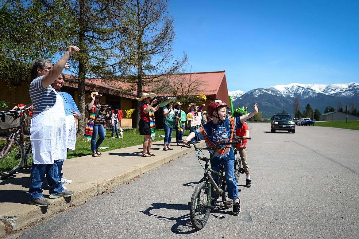 Six-year-old twins Charlie and Ryan Johnston and teachers and staff at Swan River School wave to passing truck drivers as they honk their horn at the Cinco de Mayo Parade outside the school in Bigfork on Tuesday. (Casey Kreider/Daily Inter Lake)