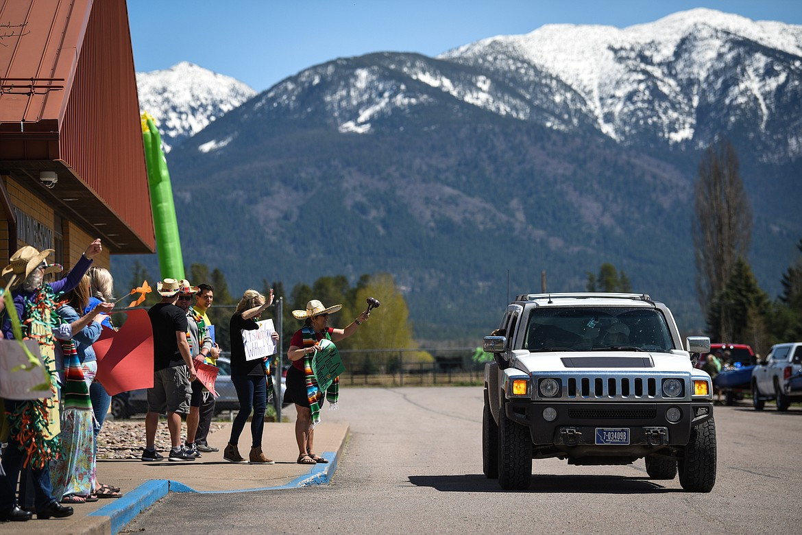 Swan River School teachers and staff wave to students and parents during a Cinco de Mayo Parade outside the school in Bigfork on Tuesday. (Casey Kreider/Daily Inter Lake)