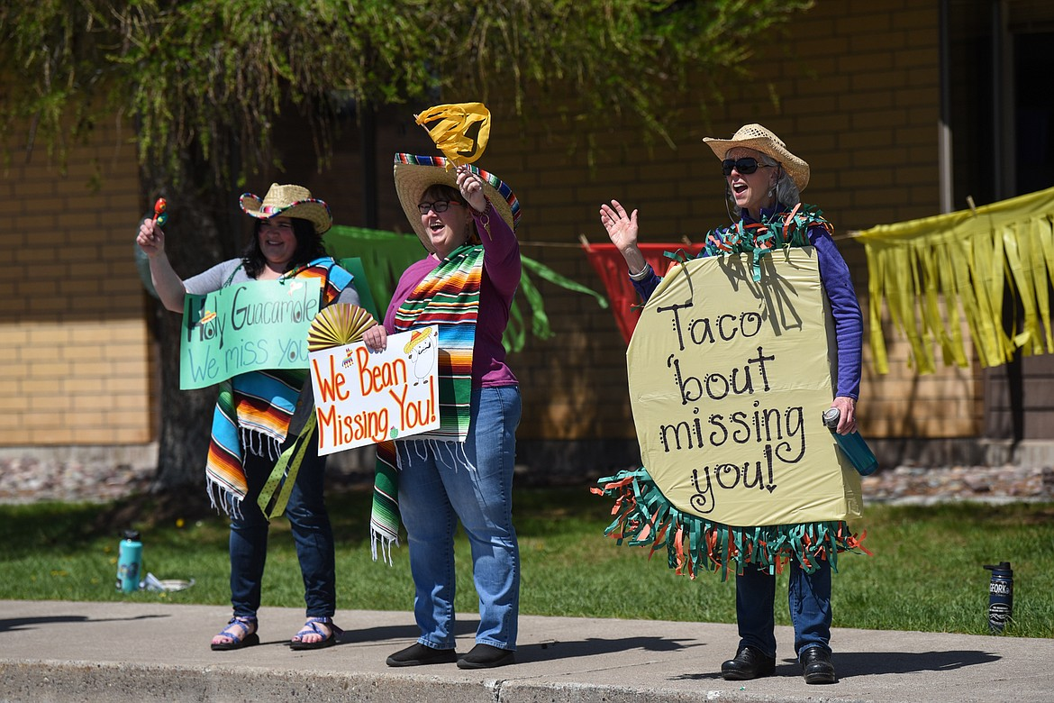 From left, first-grade teacher Christina Brevik, second-grade teacher Sherry Bradstreet and third-grade teacher Kate Butts wave and hold signs for students during a Cinco de Mayo Parade outside Swan River School in Bigfork on Tuesday. (Casey Kreider/Daily Inter Lake)