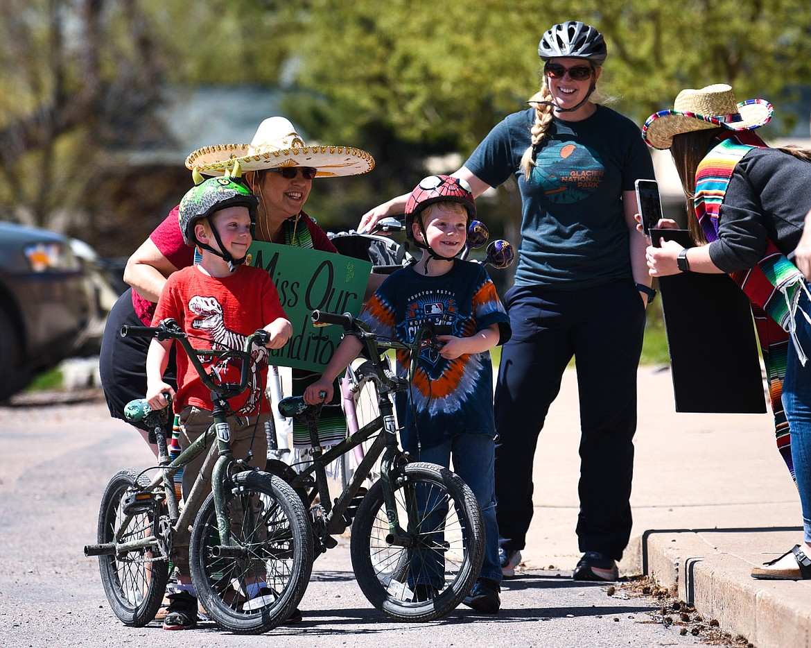 Six-year-old twins Ryan, left, and Charlie Johnston have their picture taken with their kindergarten teacher Sue Stephens during a Cinco de Mayo Parade outside Swan River School in Bigfork on Tuesday. At right is Ryan and Charlie's mother, Kim. (Casey Kreider/Daily Inter Lake)