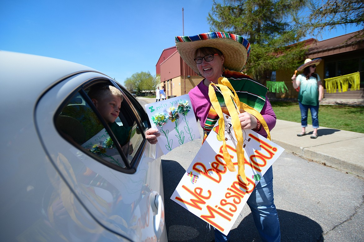 Second-grade teacher Sherry Bradstreet receives a decorative drawing from a student during a Cinco de Mayo Parade outside Swan River School in Bigfork on Tuesday. (Casey Kreider/Daily Inter Lake)