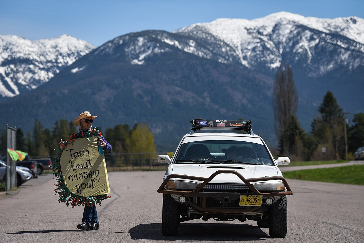 Shelly Emslie, a fifth-grade teacher at Swan River School in Bigfork, holds a sign as she speaks with a parent during a Cinco de Mayo Parade for teachers, students and staff held outside the school on Tuesday. (Casey Kreider/Daily Inter Lake)