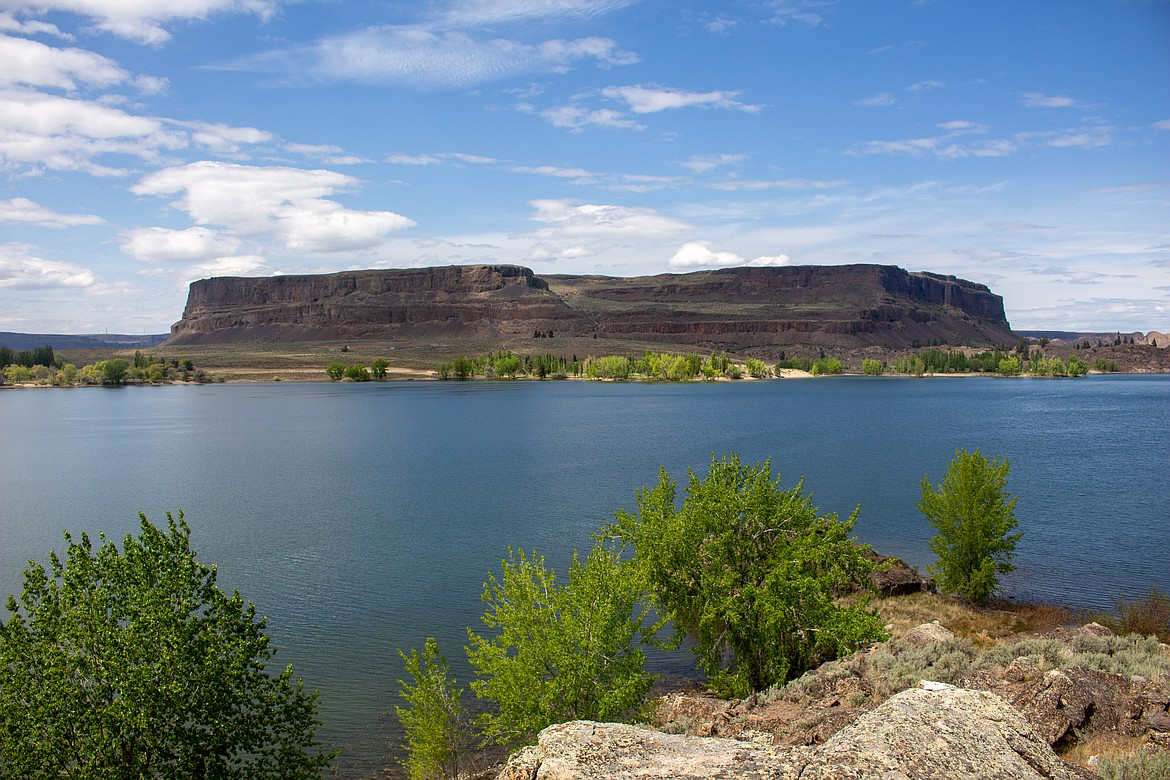 Standing alone in the distance, Steamboat Rock towers above the water and scrublands beneath it inside the state park named for the geological formation.