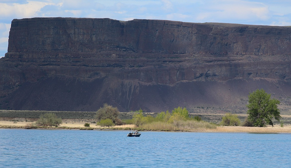 Clouds cast looming shadows on the side of Steamboat Rock in the distance as a lone angler sits in his boat on the waters of the Devil's Punch Bowl on Monday, May 4.