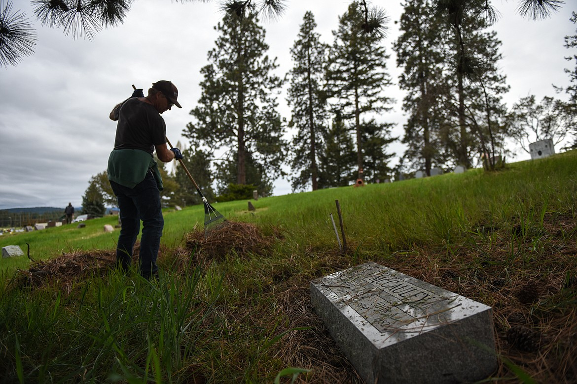 Page Rost rakes debris into piles during the annual cleanup at Lone Pine Cemetery in Bigfork on Friday, May 15. (Casey Kreider/Daily Inter Lake)