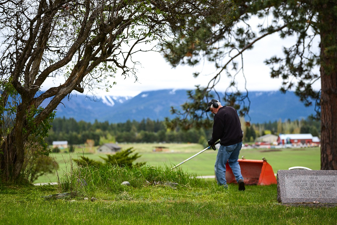 Tom Maxwell uses a weedwacker around a group of gravestones during the annual cleanup at Lone Pine Cemetery in Bigfork on Friday, May 15. (Casey Kreider/Daily Inter Lake)