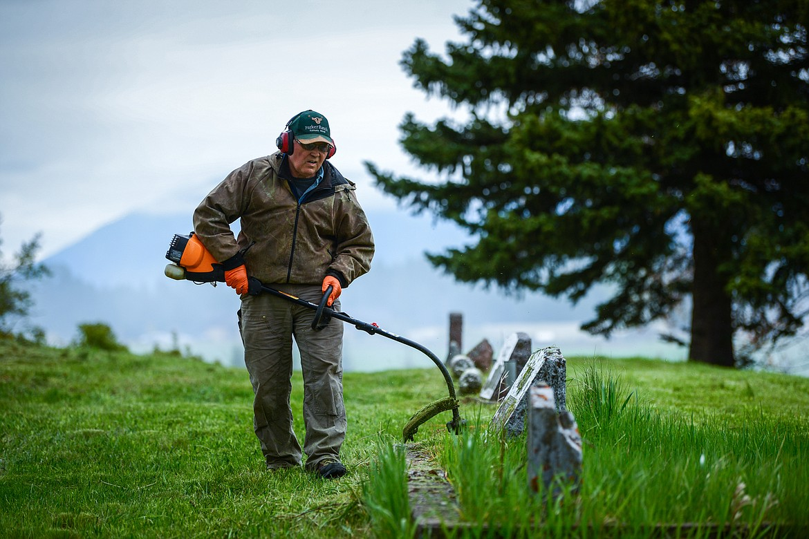 Bill Morton uses a weedwacker around a group of gravestones during the annual cleanup at Lone Pine Cemetery in Bigfork on Friday, May 15. (Casey Kreider/Daily Inter Lake)