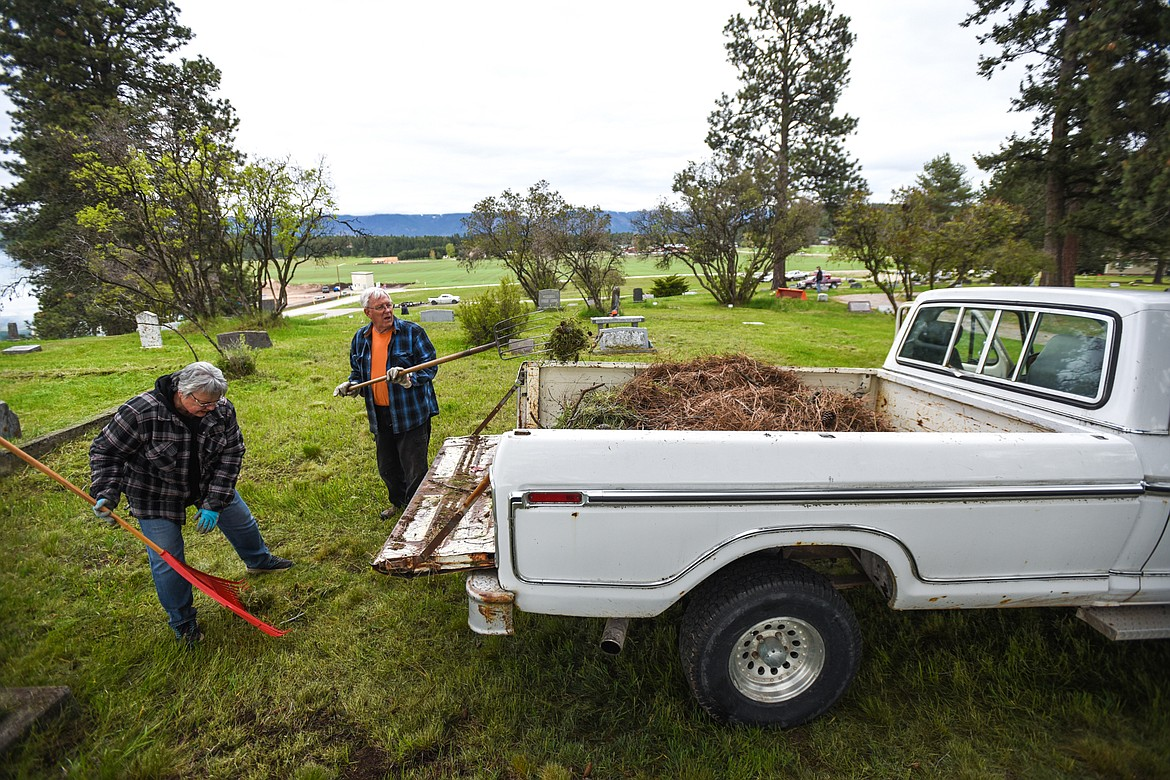 Jessie and Jeff Wade scoop debris into the back of a pickup to be transported to a burn pile during the annual cleanup at Lone Pine Cemetery in Bigfork on Friday, May 15. (Casey Kreider/Daily Inter Lake)