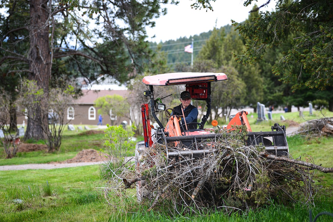 Tim Darr scoops up piles of debris during the annual cleanup at Lone Pine Cemetery in Bigfork on Friday, May 15. (Casey Kreider/Daily Inter Lake)