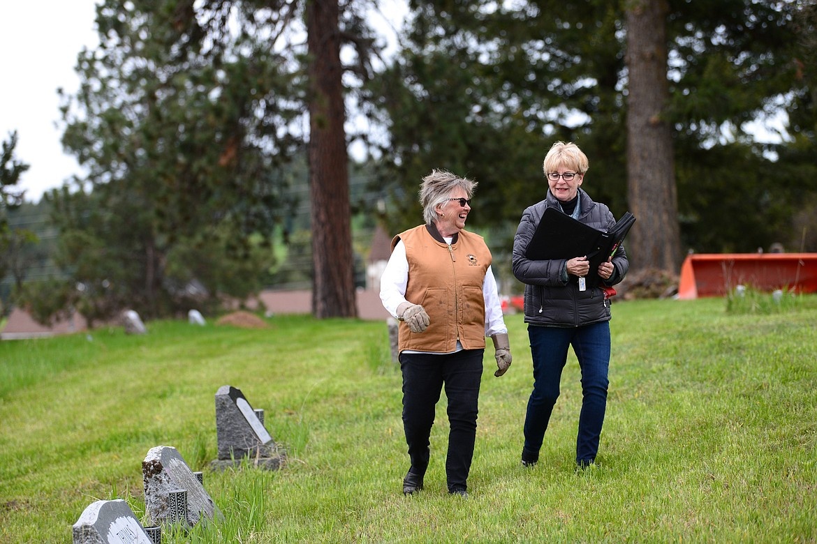 Arlene Wilson, left, and Darlene Smith take a break from cleaning up debris at Lone Pine Cemetery in Bigfork on Friday, May 15. (Casey Kreider/Daily Inter Lake)