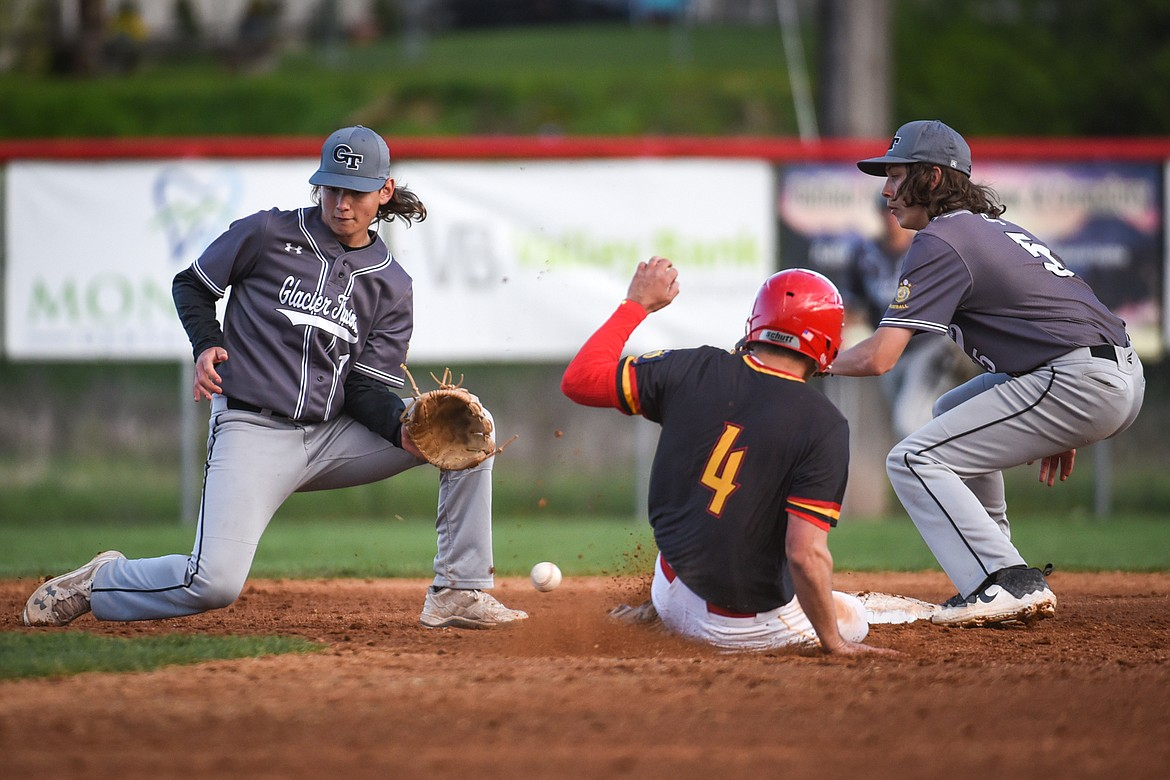 Kalispell Lakers AA's Kobe Burland steals second base as the throw to second skips between Glacier shortstop Stevyn Andrachick and second baseman George Robbins in the first inning at Griffin Field on Saturday. (Casey Kreider/Daily Inter Lake)