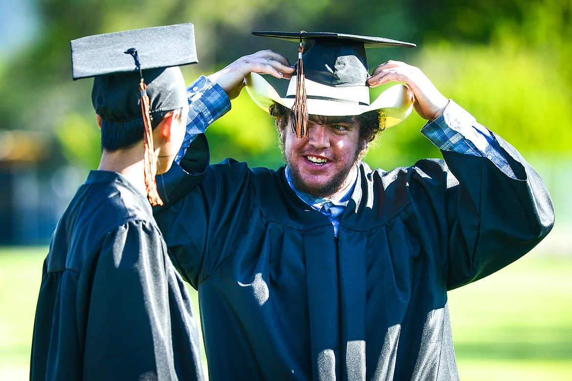 Mike Miller, right, adjusts his cap atop his cowboy hat as he talks with classmate John Weil before the Flathead High School Class of 2020 commencement ceremony at Legends Stadium on Friday, May 29. (Casey Kreider/Daily Inter Lake)