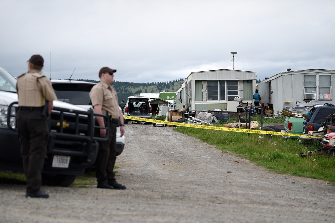 Deputies with the Flathead County Sheriff's Office stand at the scene of an alleged homicide along Cobbler Village Terrace west of Kalispell on Tuesday, June 9. (Casey Kreider/Daily Inter Lake)