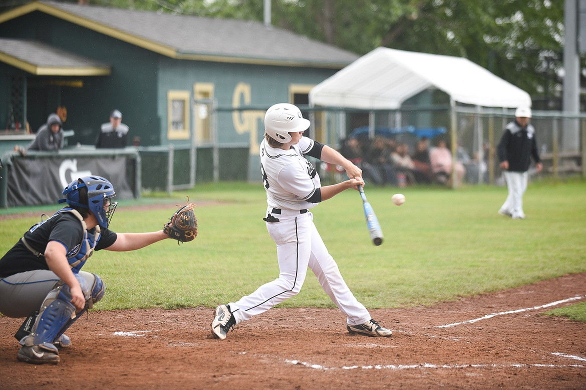 Zach Veneman connects on a pitch in the first of two Sunday battles against the Libby Loggers. (Daniel McKay/Whitefish Pilot)