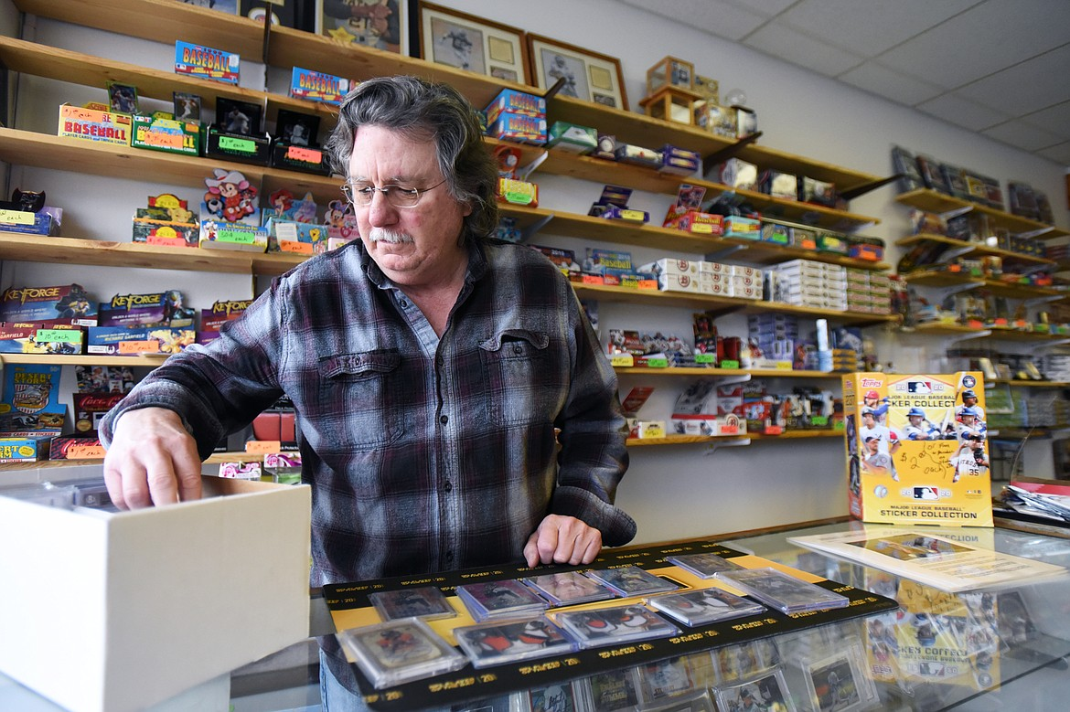 Tony Sibert, owner at Sports Cards Plus, sorts through cards at the front counter in Evergreen on Wednesday, June 10. (Casey Kreider/Daily Inter Lake)