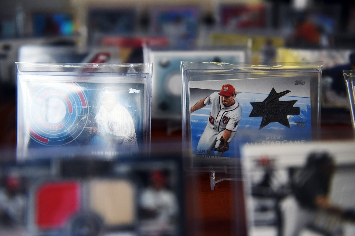 Sports cards reflect the light inside a display case at Sports Cards Plus in Evergreen on Wednesday, June 10. (Casey Kreider/Daily Inter Lake)